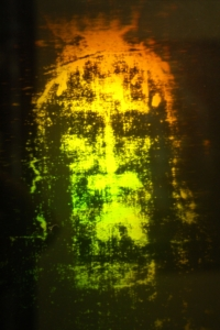 Photograph 01. Hologram face with letters on solid oval object