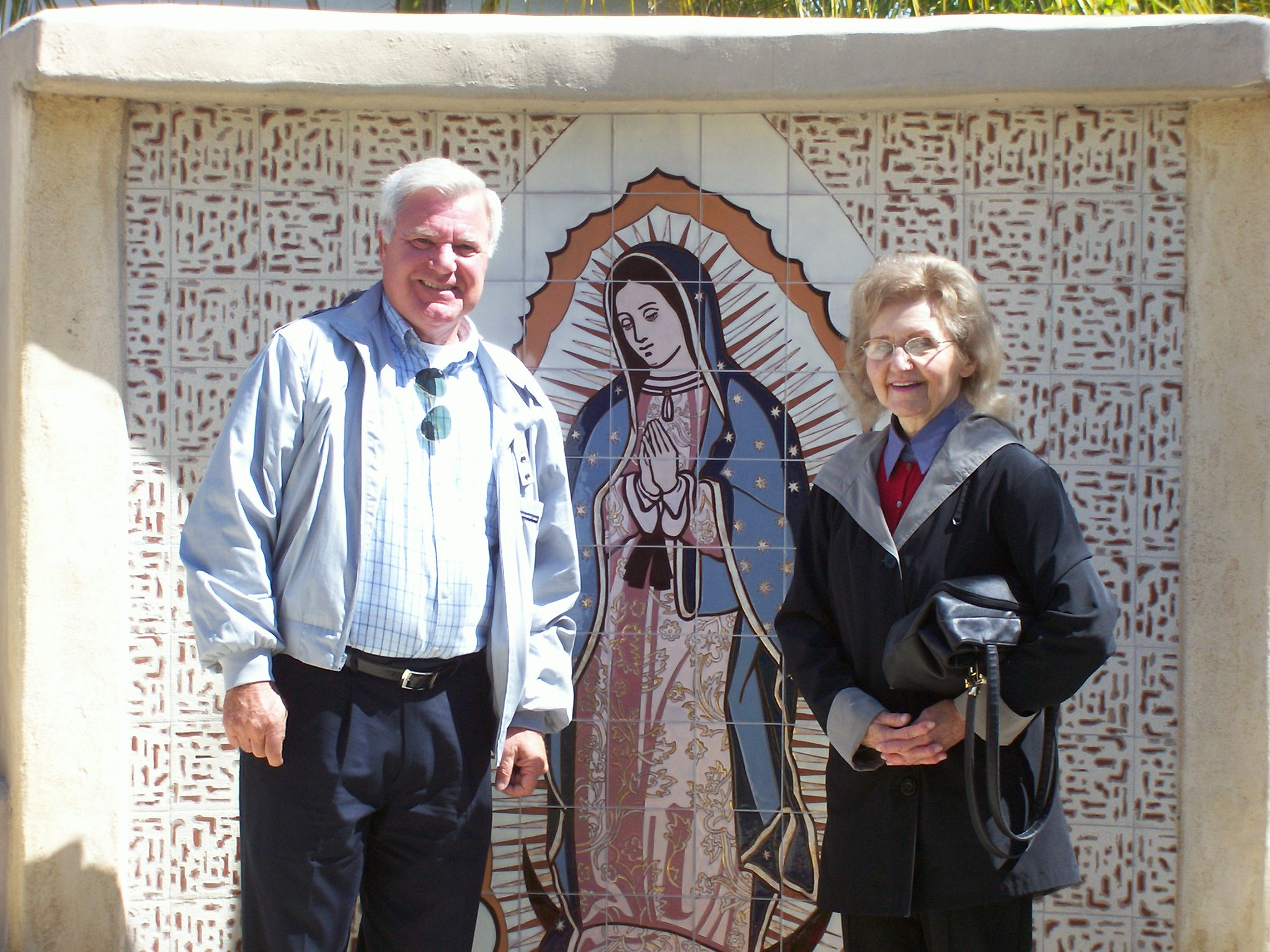 Photo 9. Isabel and Dr. Soons in front of tile work of Maria de Guadalupe