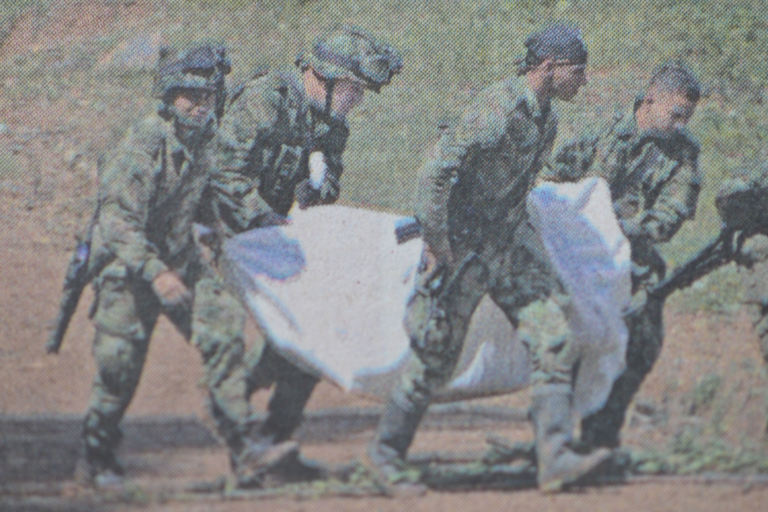 Photo 3. Four people carrying dead body